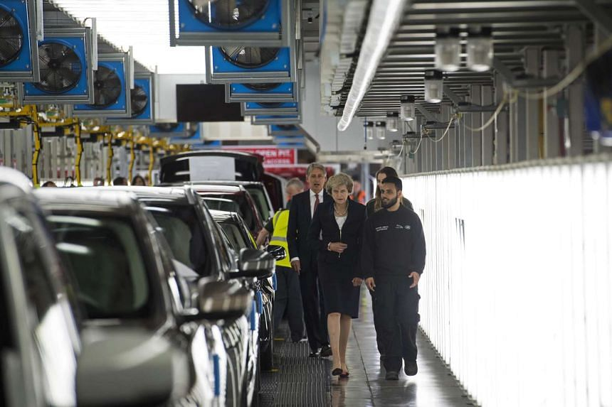 British Prime Minister Theresa May (centre) and Chancellor of the Exchequer Philip Hammond visit the Jaguar Land Rover factory on Sept 1, 2016 in Solihull.