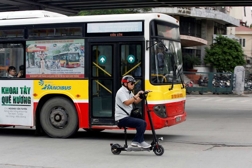 A man rides a scooter next to a bus on a street in Hanoi, Vietnam, on Sept 30, 2016.
