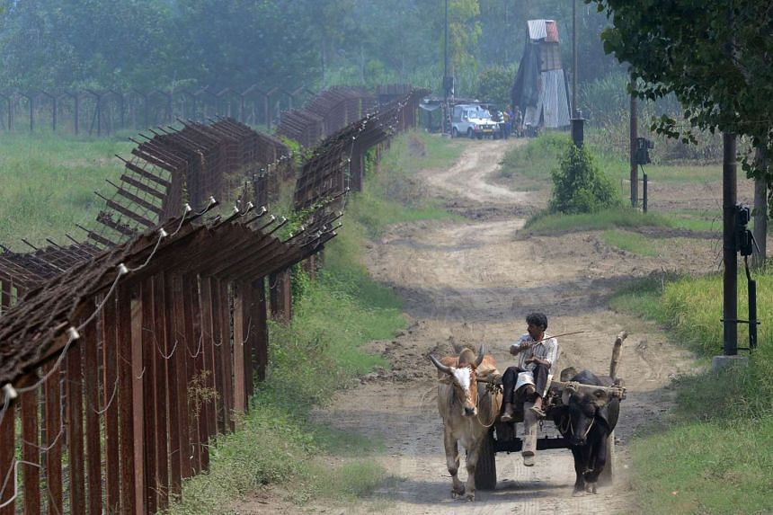 An Indian farmer on a cart passes along the Indian-Pakistan Border fence, about 20km from Gurdaspur, on Oct 3, 2016.