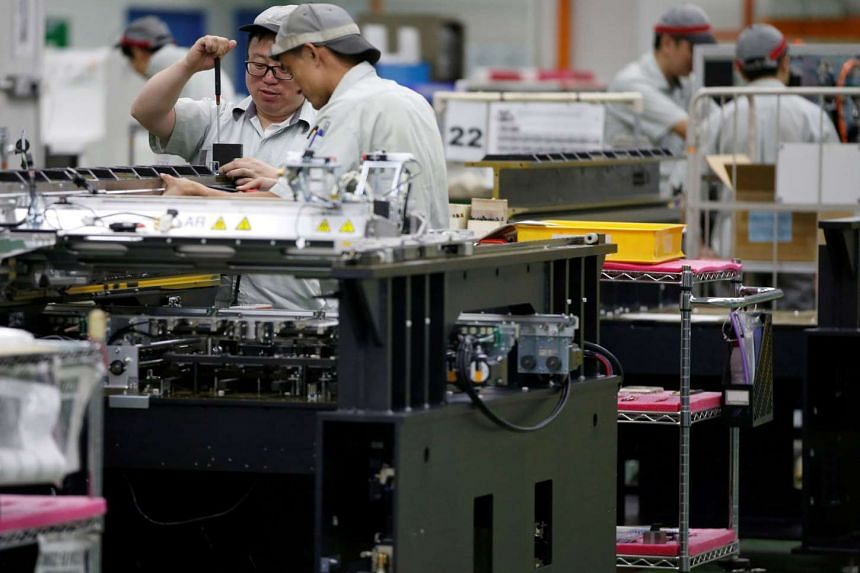 Employees seen by their workstations at a printed circuit board assembly factory in Singapore.