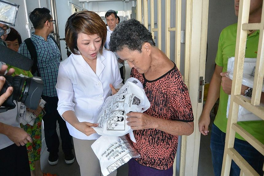 Dr Lily Neo, MP for Jalan Besar GRC and chairman of Jalan Besar Town Council, distributing trash bags to residents of Block 2 in Jalan Kukoh as part of a new campaign to arrest high-rise littering in the area.