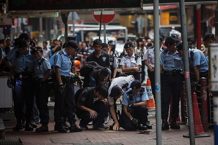 Police officers examining the scene of a knife attack on a man in Hong Kong's Yau Ma Tei district yesterday. Police say they fired shots to stop five or six men from attacking another man. Two assailants and the knife attack victim were wounded.