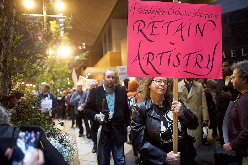 Musicians of the Philadelphia Orchestra on strike (above) over pay issues just before their season-opening gala concert in Philadelphia last Friday.