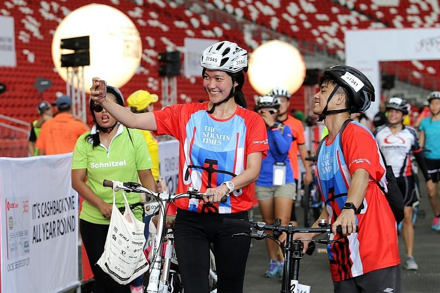 It's wefie time as two participants pose proudly after finishing The Straits Times Ride at yesterday's OCBC Cycle. Nearly 7,000 riders took to the streets of downtown Singapore in the nation's largest mass cycling event to take part in the 42km The S