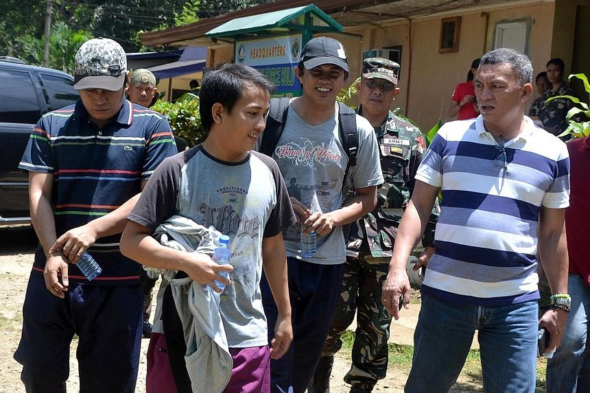 The three Indonesian sailors (from left), accompanied by soldiers and local officials, after their release by Abu Sayyaf rebels yesterday.