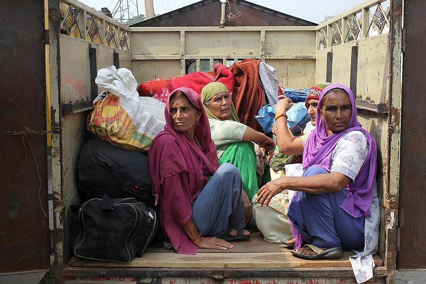 Indian villagers sitting inside a vehicle as they are evacuated from their village near the border with Pakistan. Tensions between the two states have risen rapidly, with Pakistan reacting furiously to Indian military raids that were carried out in r