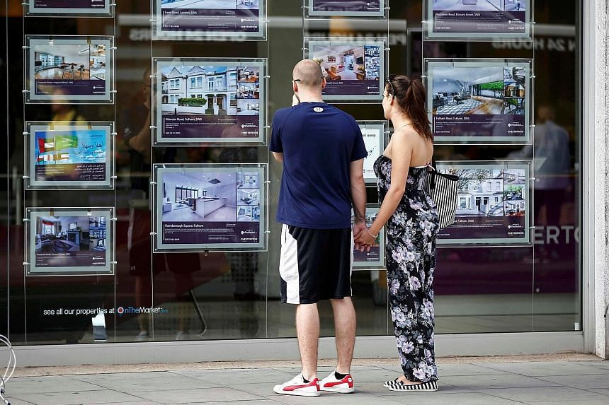 """A couple viewing advertisements of properties for sale in an estate agency's window in London. Mayor Sadiq Khan has announced the launch of an unprecedented inquiry into foreign home ownership and """"dirty money"""" that is allegedly being used to buy pro"""
