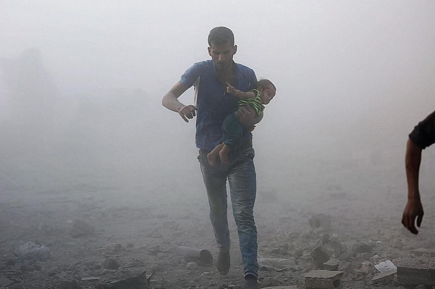 A Syrian man with a child fleeing from a reported air strike on a rebel-held area near Damascus.