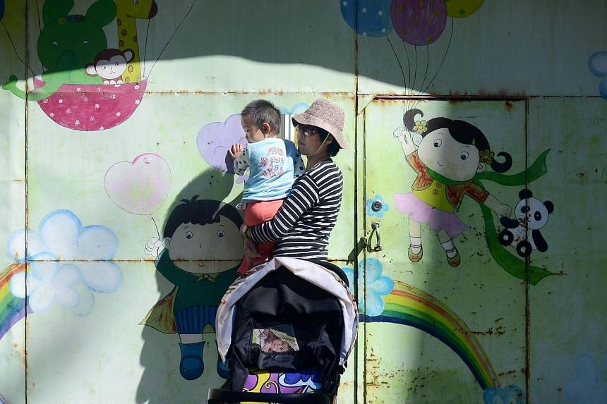 A woman carrying a child outside a nursery school in Beijing, on Sept 28, 2016.