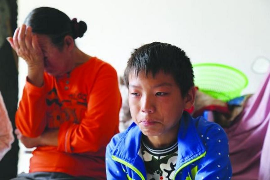 Shi Luyao, 11, cries as he recounts going to the hospital to receive treatment for leukaemia on his own.