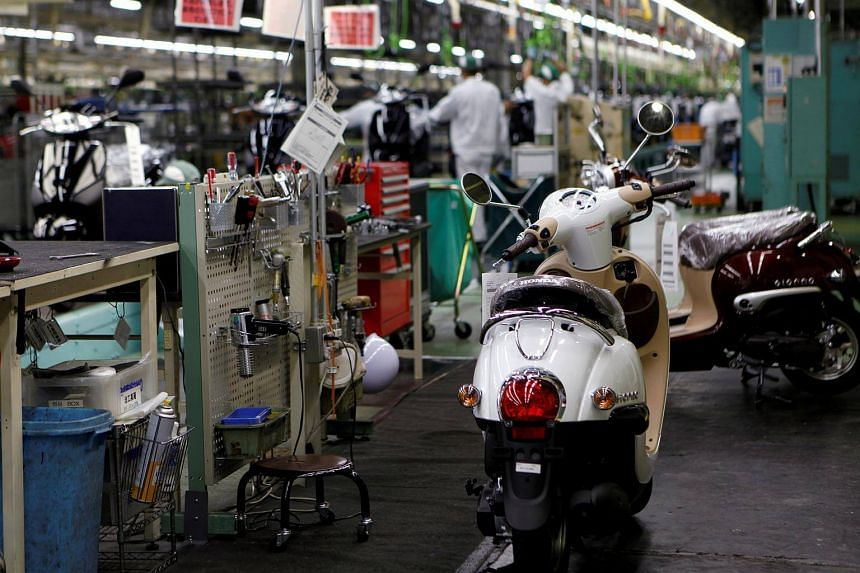 Honda Motor's scooters are seen in front of an assembly line at Honda's Kumamoto factory in Ozu town, Kumamoto prefecture, Japan, on Sept 13, 2016.