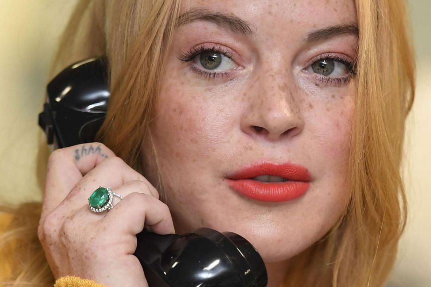 Lindsay Lohan speaks on a telephone during a charity day at BGC Partners in London on Sept 12, 2016.
