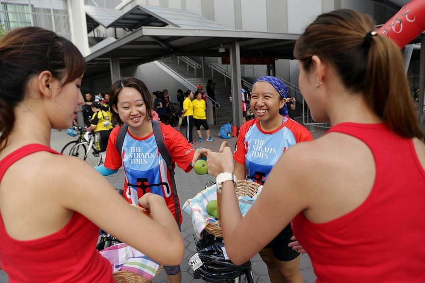 Sportive girls Mandy Wong (left), 24, and Katherine Yang (right), 27, distributing fruit to cyclists (second from left) Cassandra Lew, 26, and Carmen Kee, 26, after the ride ended.