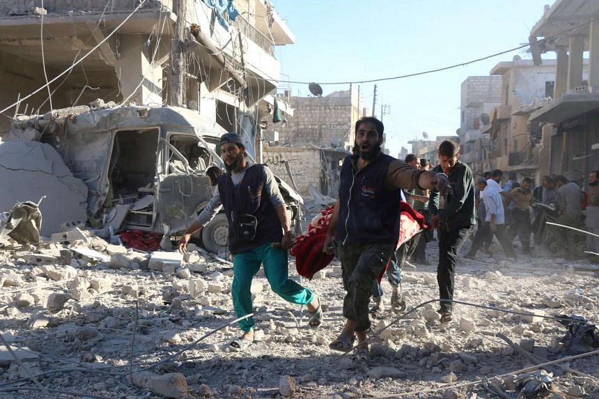 Syrian volunteers carry an injured person on a stretcher following Syrian government forces airstrikes on a rebel held neighbourhood in Aleppo.