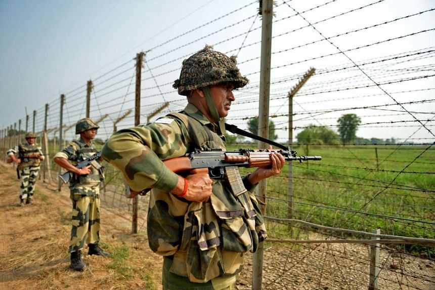 Indian Border Security Force (BSF) soldiers take up positions at an outpost along a fence at the India-Pakistan border on Sunday (Oct 2, 2016).