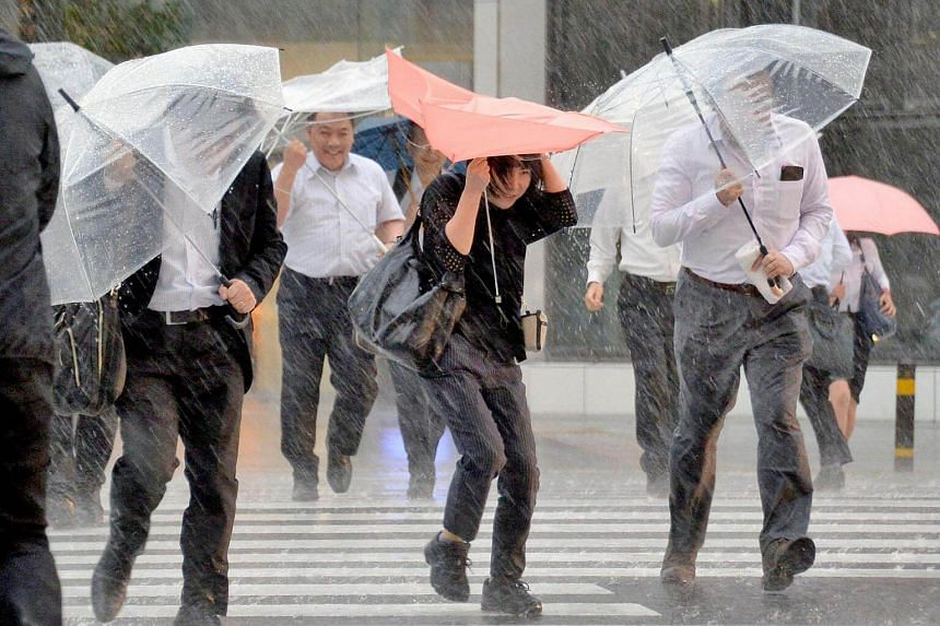 Pedestrians holding umbrellas struggle against strong wind and heavy rains caused by Typhoon Malakas in Nagoya, central Japan.