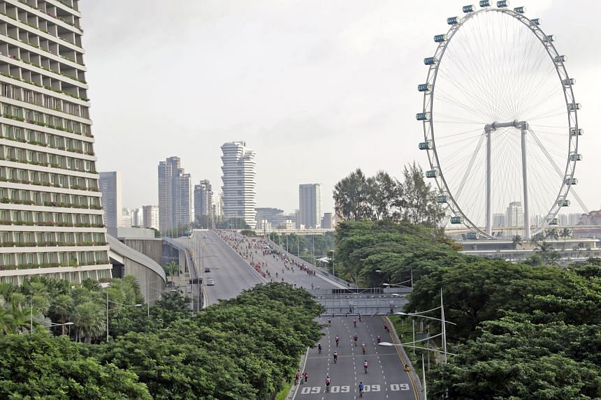 Cyclists riding along Sheares Avenue, past the iconic Singapore Flyer, during yesterday morning's OCBC Cycle. Over 6,800 cyclists took part this year, the eighth edition of the annual event.