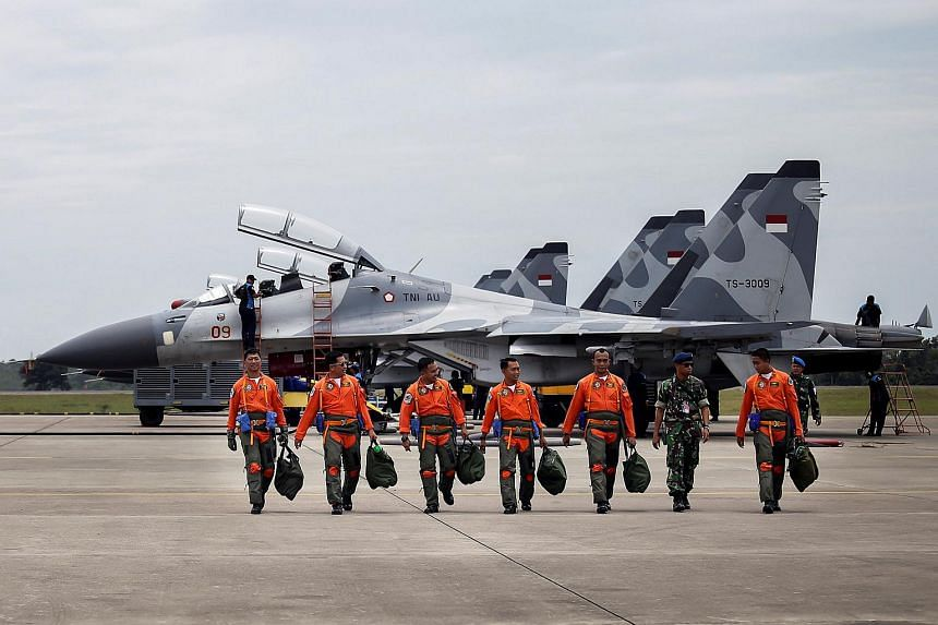 Indonesian Air Force Sukhoi fighter pilots and crew walk across the tarmac after training for an upcoming military exercise on Oct 3, 2016.