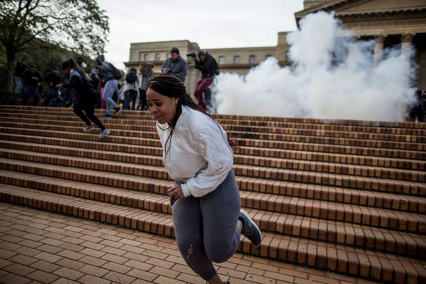 A student runs from an exploding stun grenade thrown by anti-riot police at the Witwatersrand University in Johannesburg on Oct 4, 2016.