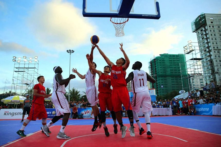 Players compete during a men's 3-on-3 basketball match between Qatar (white) and Vietnam (red) at the Asian Beach Games in Danang.