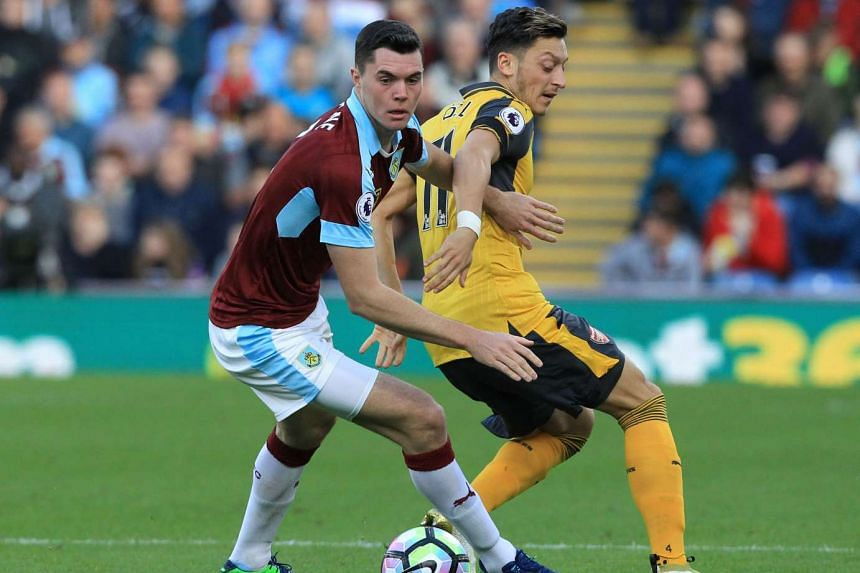 Burnley's English defender Michael Keane (in red) vies with Arsenal's German midfielder Mesut Ozil on Oct 2, 2016.