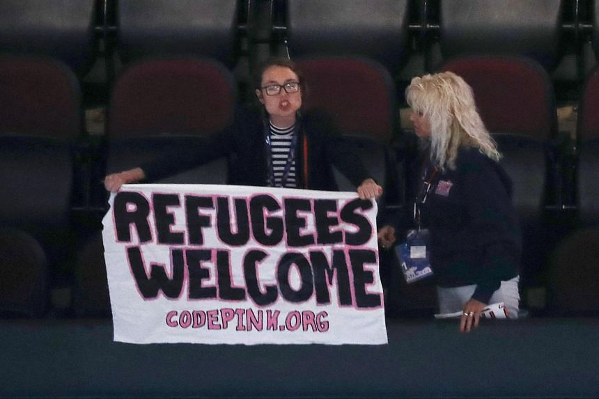 """A protester holds up a sign reading """"Refugees Welcome"""" at the Republican National Convention in Cleveland, Ohio, on July 18, 2016."""