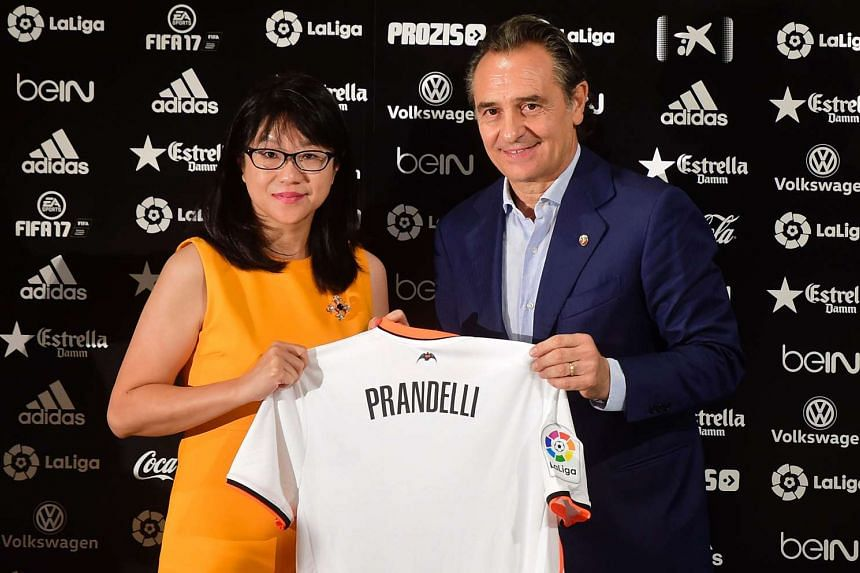 Valencia's Italian coach Cesare Prandelli (right) holds his new team's jersey as he poses with Valencia's Singaporean President Lay Hoon Chan during his presentation to media.
