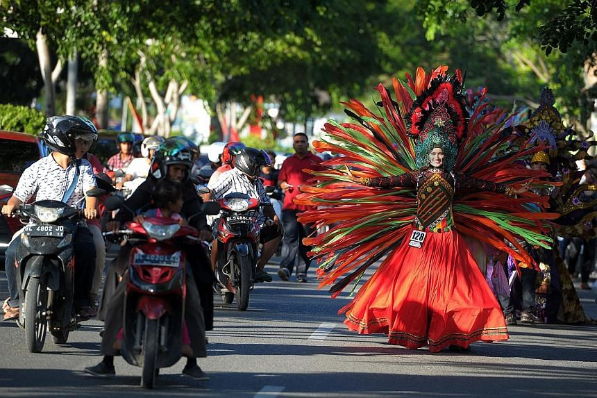An Acehnese model (left) dressed in an explosion of colours brings traffic to a stop at a fashion show along the streets during Aceh Fashion Week in Banda Aceh, while another model (above) presents a creation by a local designer. Most of the designs