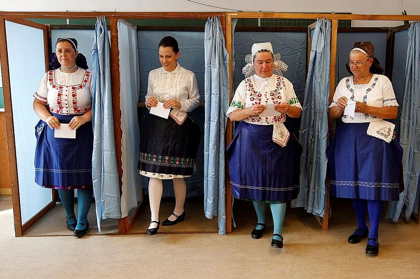 Hungarian women in traditional attire at Sunday's referendum on EU migrant quotas. Just 40 per cent of about 8.26 million eligible people cast a valid vote, less than the 50 per cent needed to legitimise the result.