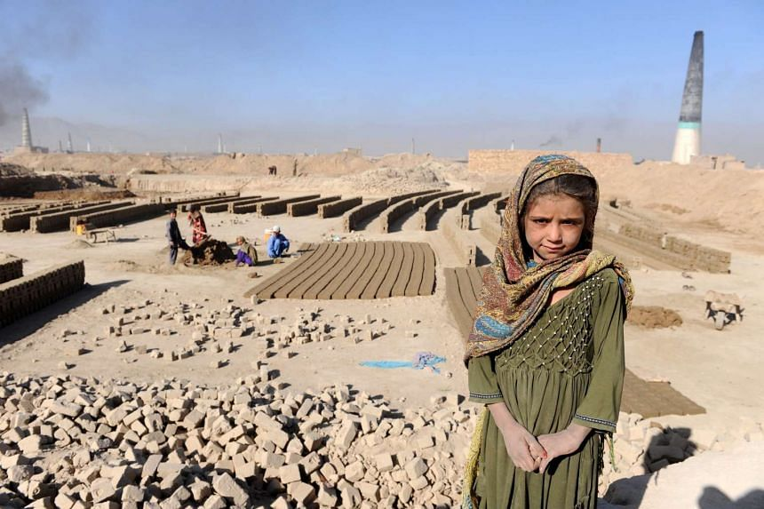 An Afghan girl works at a brick kiln in Kabul. World powers are convening in Brussels to raise billions more dollars for Afghanistan to keep the country running until 2020.