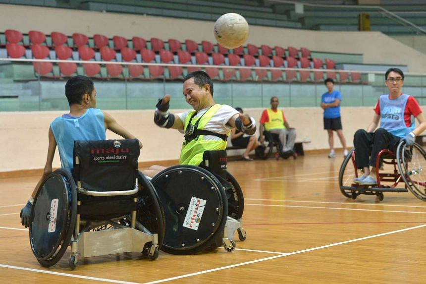 Mr Tan Whee Boon passing the ball during a wheelchair rugby session on Oct 4, 2016.