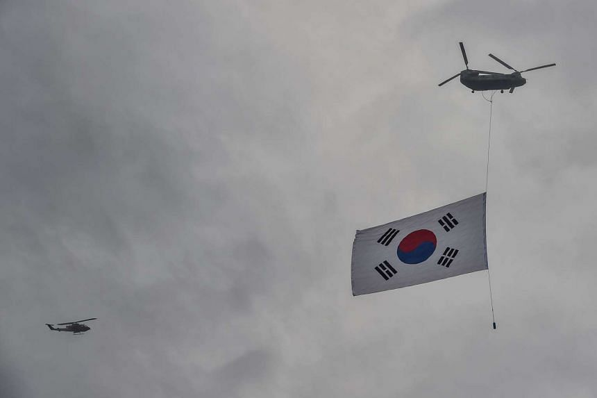 A South Korean flag is displayed beneath a military helicopter during a commemoration event marking Armed Forces Day.