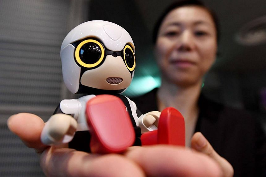 A staff member presenting a Kirobo Mini robot during a press conference in Tokyo, Japan.