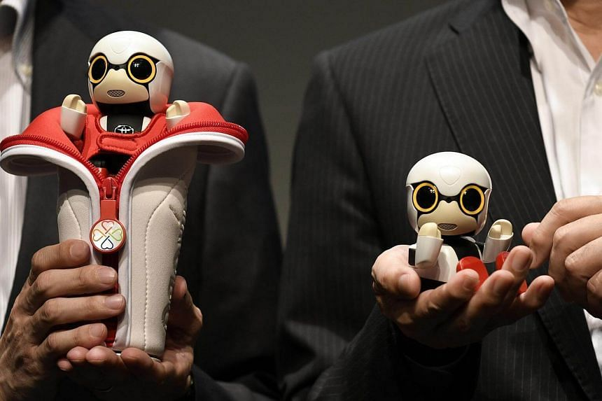 Senior Managing Officer Moritaka Yoshida (right) and Project General Manager Fuminori Kataoka (left) posing with Kirobo Mini robots during a press conference in Tokyo, Japan. PHOTO: EPA