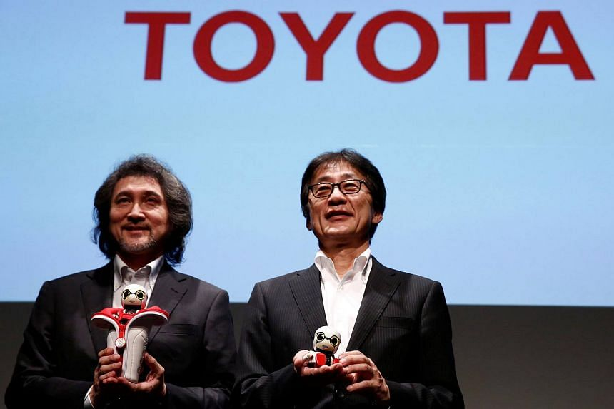 Toyota Motor Corp's Senior Managing Officer Moritaka Yoshida (right) and Kirobo Mini's chief design engineer Fuminori Kataoka pose with Kirobo Mini robots at a news conference in Tokyo, Japan.
