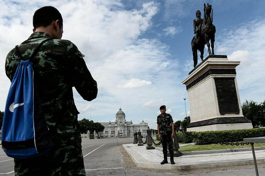 Soldiers take pictures in front of King Rama V statue and Ananta Samakhom Throne Hall in Bangkok.