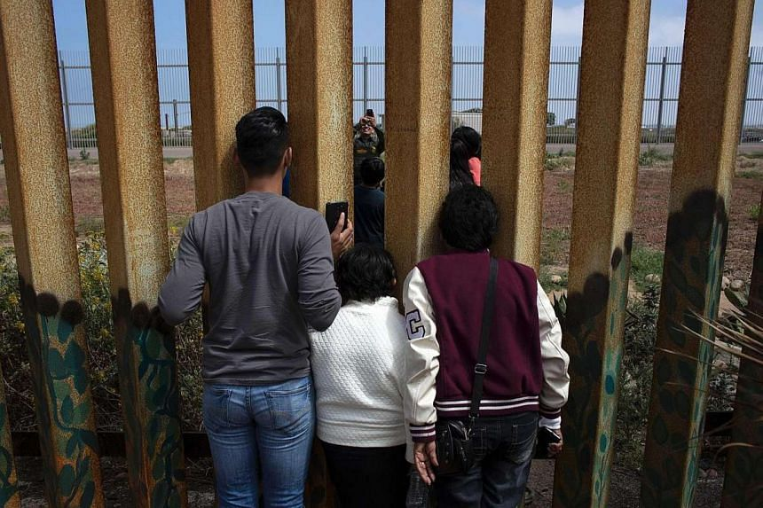 A US Border Patrol agent taking a family portrait for members of the Rosete-Quintana family on both sides of the US-Mexico border in Tijuana, north-western Mexico. Republican presidential nominee Donald Trump wants to extend the wall along the border