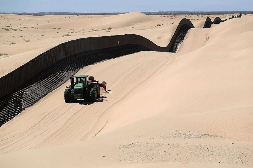 A sand plough removing sand drifts along the US-Mexico border fence in the Imperial Sand Dunes area, California. Without daily sand removal, the dunes would cover the fence and illegal immigrants and smugglers could simply walk over it.