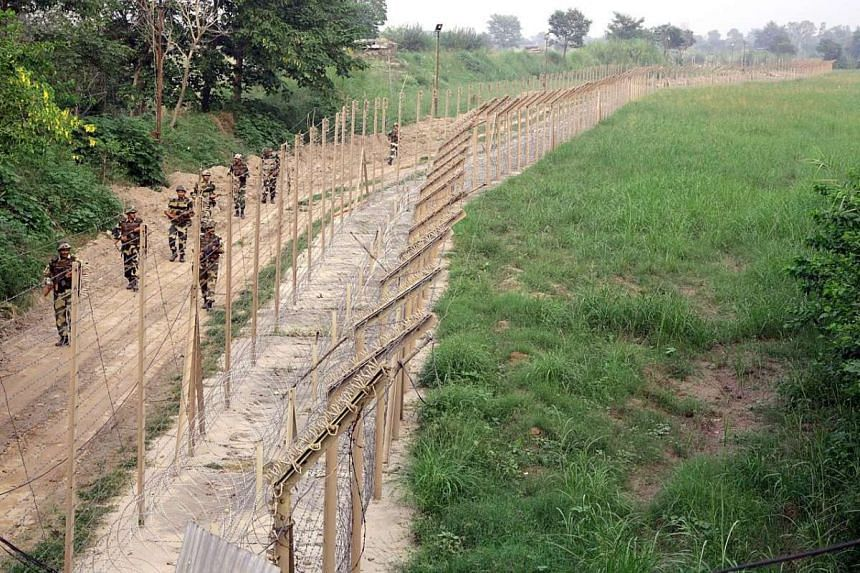 Indian Border Security Force soldiers patrolling the fence at the India-Pakistan border about 60km from Jammu last month. The soldiers are on a high alert due to heightened tensions after a recent terror attack.