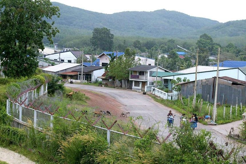 Thai houses along the border fence separating Malaysia and Thailand at Padang Besar, Perlis. The two countries are considering a border wall to combat transnational terrorism and smuggling along their border.