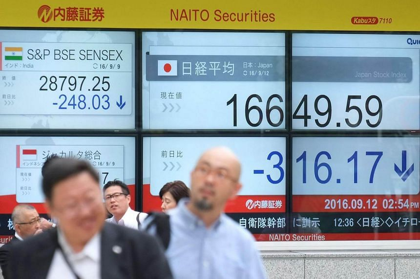 Pedestrians walk past an electric quotation board displaying the Nikkei key index of the Tokyo Stock Exchange.