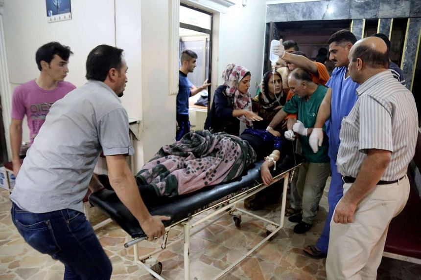 People carry a wounded woman on a stretcher inside the Al Rahma hospital after an explosion killed at least 22 people in an attack targeting a wedding party in the northeastern province of Hasakeh, Syria.