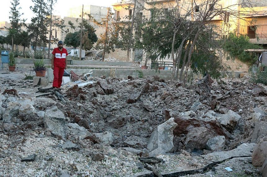 A Syrian medical staff member inspects the damage at the site of a medical facility after it was reportedly hit by Syrian regime barrel bombs on Oct 1, 2016, in the rebel-held neighbourhood of al-Sakhour, Aleppo.