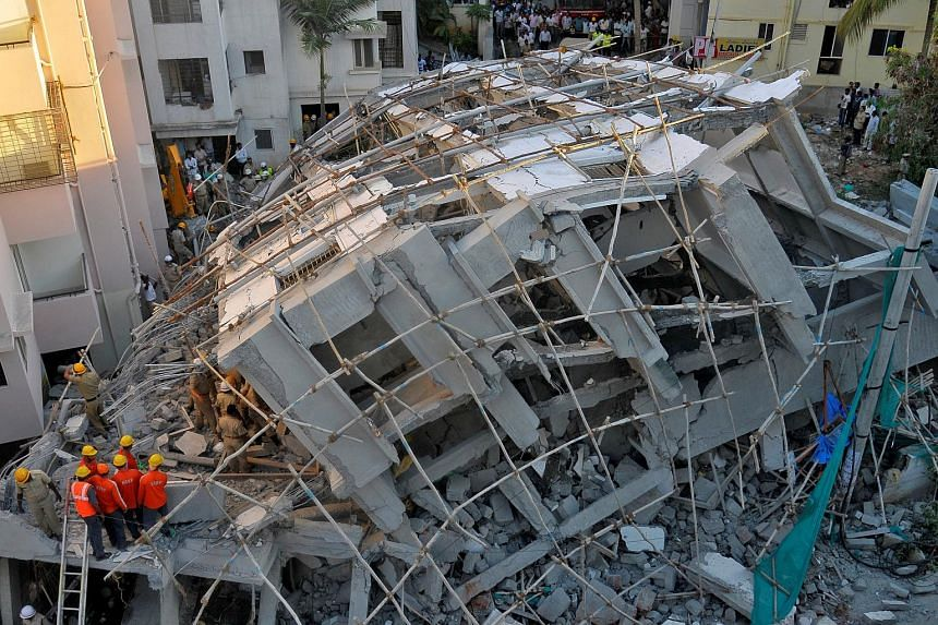Police and rescue workers look for survivors in the rubble at the site of a collapsed under construction building in Bengaluru, India on Oct 5, 2016.
