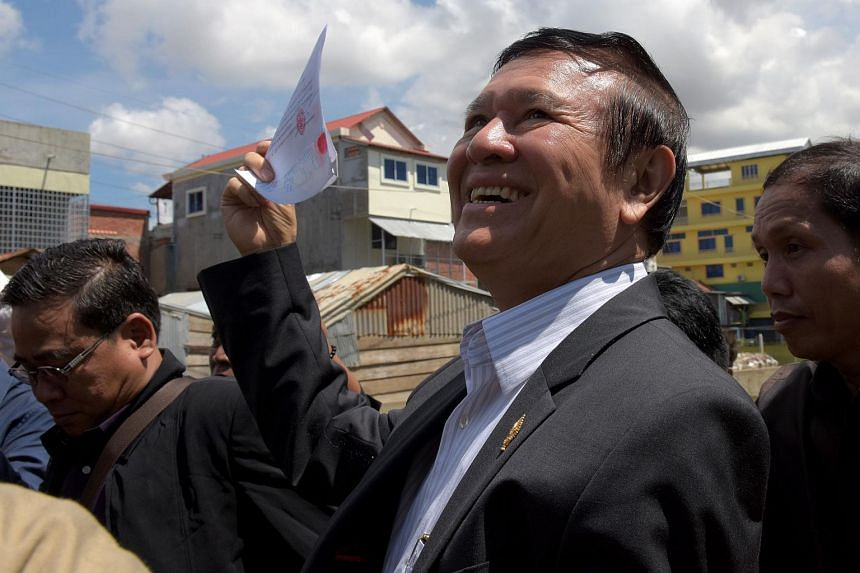 Mr Kem Sokha, Cambodia's opposition party deputy leader, shows his voter documents after registering for local 2017 elections in Phnom Penh on Oct 5, 2016.