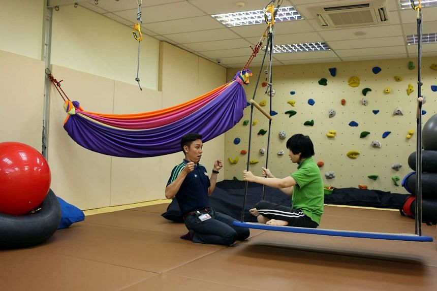 A staff member with a patient in the sensory integration gym at the Institute of Mental Health in Buangkok.