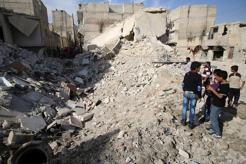 People inspect a damaged site after airstrikes in the rebel held Karam Houmid neighbourhood in Aleppo, Syria on Oct 4, 2016.
