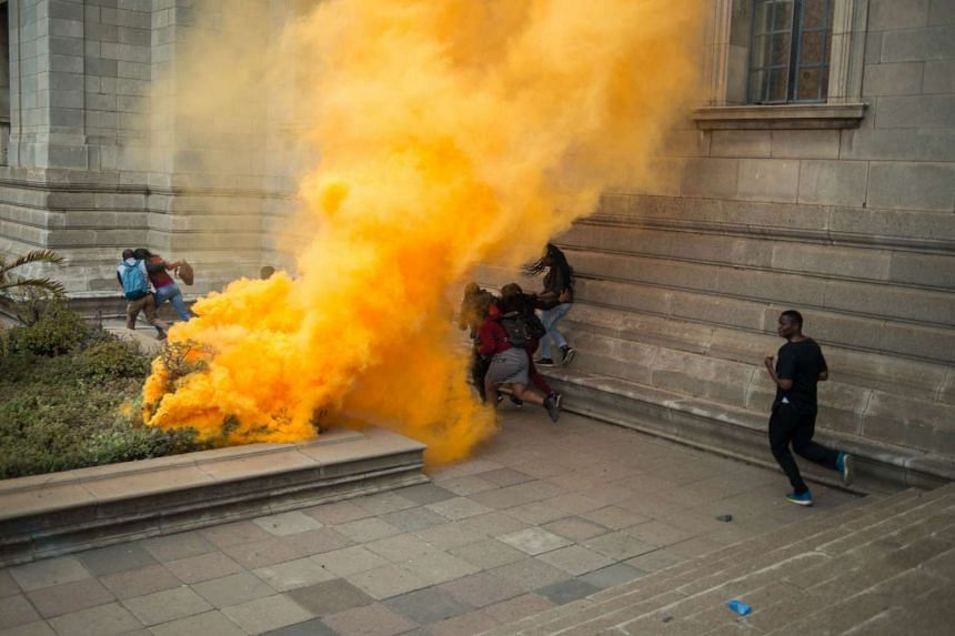 Student run among smoke bombs during a mass protest of the Fees Must Fall movement at the University of Witwatersrand in Johannesburg on Oct 4, 2016.