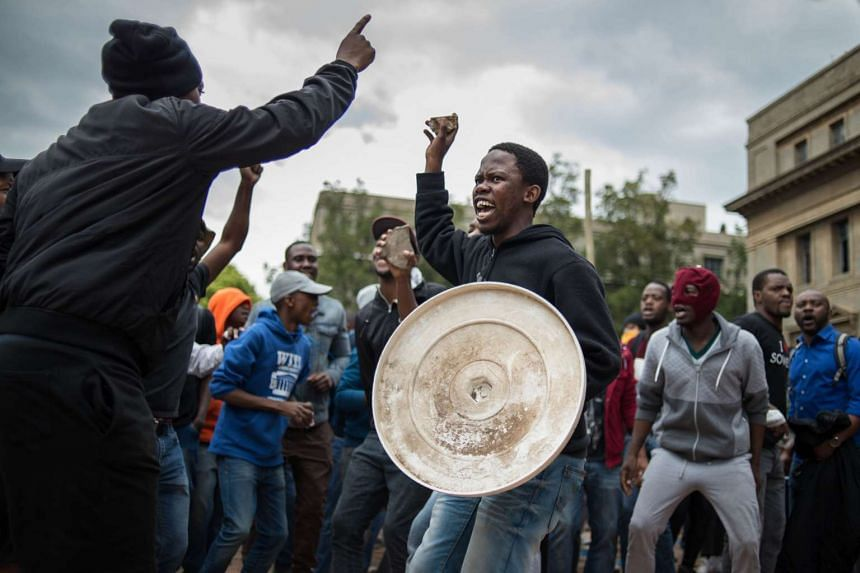 Students hold stones as they gesture during a mass protest of the Fees Must Fall movement at the University of Witwatersrand in Johannesburg on Oct 4, 2016.