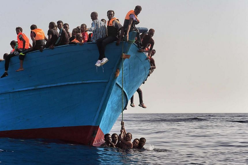 Migrants wait to be rescued by members of Proactiva Open Arms NGO in the Mediterranean Sea, some 12 nautical miles north of Libya, on Oct 4, 2016.